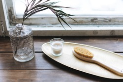 Details of interior, aromatic candle in glass and wooden brush with natural bristles on the metal tray on wooden window sill