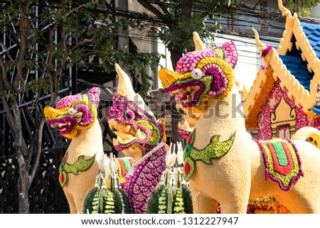 Details of mystical creatures decorated with fresh flowers on a float used in the February Flower Festival Parades in the City of Chiangmai, Thailand. #1312227947