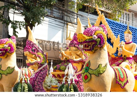 Details of mystical creatures decorated with fresh flowers on a float used in the February Flower Festival Parades in the City of Chiangmai, Thailand. Oriental flower decorative arts.