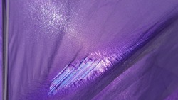Details of old beach sunshade. Purple lacerated fabric surface with worn textile structure closeup. Sun is shining through torn textile tent with threads inside hole in fabric.