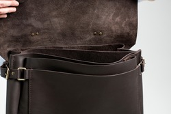 Details of open brown men's shoulder leather bag for a documents and laptop on the shoulders of a man in a blue shirt and jeans with a white background. Satchel, mens leather handmade briefcase.