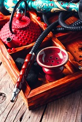 Details of smoking hookah,cast iron red teapot in wooden box