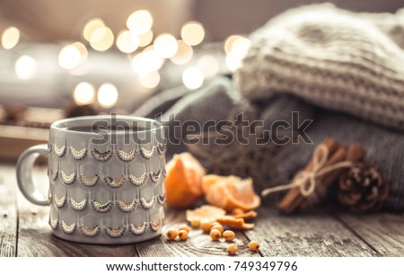 Details of still life in the home interior living room. Beautiful Cup of tea with tangerines and sweaters on wooden background . Cosy autumn-winter concept #749349796