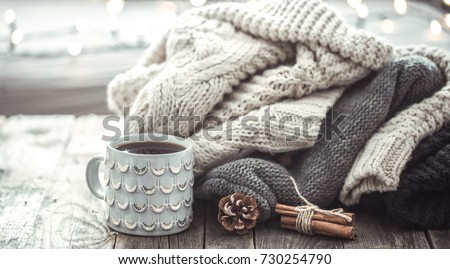 Details of still life in the home interior living room. Beautiful tea Cup and shoes on wooden background . Cosy autumn-winter concept #730254790