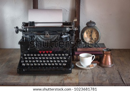 Details of still life in the home interior. Vintage retro journalist desktop with cup of coffee, old alarm clock, gas lamp, books, typewrittert  on wooden background in rustic style.