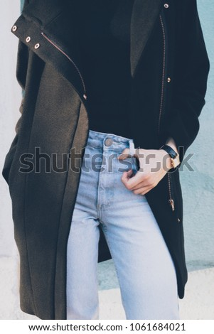 Details of stylish winter, spring or autumn outfit. Cropped photo of slender young woman wearing black coat, blue high waist jeans and gold wrist watches. Fashionable girl posing at sunny day outside. #1061684021