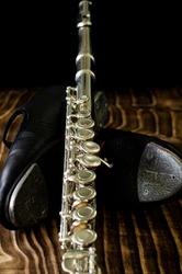 details of tap shoe and silver cross flute, black background, short depth of field.