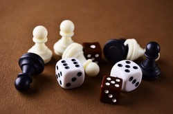 Details of the board game dice and chess pieces close-up lie on the brown table. Play board games. High quality photo
