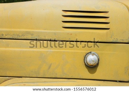 Details of the bonnet of a Soviet military truck. Side turn signal lights. Design elements and details of an old camouflage surface with exfoliated paint on a military truck. Car detail. Close-up
