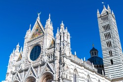 Details of the facade of the Cathedral of Siena (Duomo di Siena) and its tower. Siena. Italy