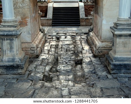 Details of the Hadrian's Gate in Antalya, Turkey. Stone pavement with deep grooves carved by wheels.