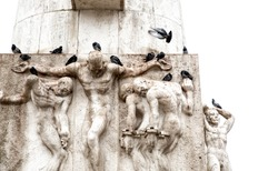 Details of the sculptures of the obelisk of Dam square with pigeons resting above