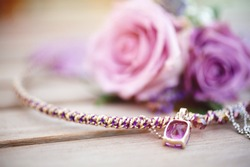 Details of the wedding day. Wedding morning of the bride. Delicate necklace with pink ruby stone, boutonniere for groom in a background.