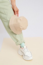 Details of trendy casual spring summer fresh outfit. Girl in studio wearing khaki jeans and stylish white sneakers.  Bucket hat. No face. Minimalist vegan clothing concept