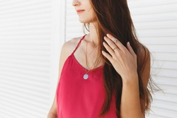 Details of trendy casual summer or spring outfit. Woman wearing pink cami top, gold rings and necklace standing near white roller door. Street fashion.