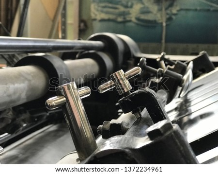 details of vintage printing presses gleaming in the sunlight