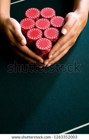 Details of woman holding pile of gambling chips on table in casino
