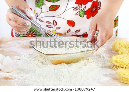 Details of woman's hands mixing  dough