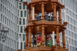 Details of wooden Christmas carousel with nativity scenes and wood sculptural Christmas characters. Rustic wood Christmas pyramid in front of skyscraper walls. Famous fair Christmas market in Germany