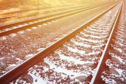 Details snowy Russian winter railway under bright sunlight. The rails and sleepers under the December snow. Russian Railways in detail
