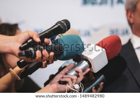 Details with the hands of journalists holding worn out microphones in front of a politician during a press conference #1489482980