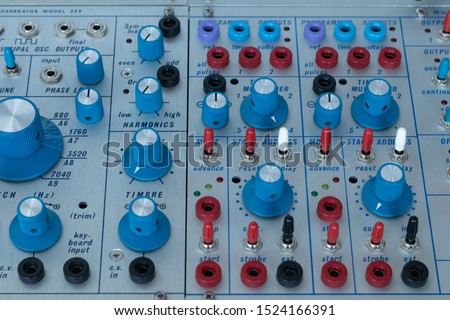Detailshot of colorful knobs and switches from a modular synthesizer.
