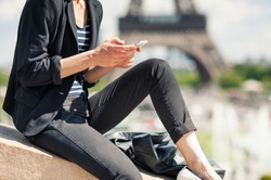 Deteail of young woman using mobile phone in front of the Eiffel Tower. Paris, France. Filtered image.