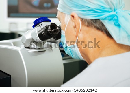 Detecting eyesight problems. Professional hard working doctor looking into the lens while detecting eyesight problems