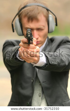 detective aiming with a gun into the camera