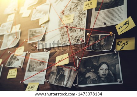 Photo of  Detective board with photos of suspected criminals, crime scenes and evidence with red threads, selective focus, retro toned