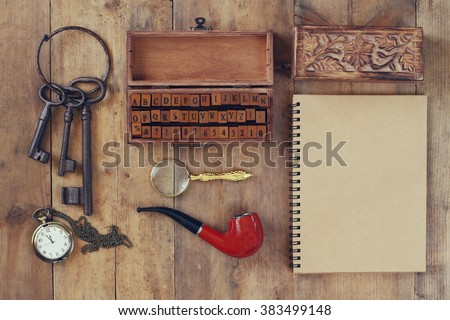 detective concept. Private Detective tools: magnifier glass, old keys, smoking pipe, notebook. top view. vintage filtered image