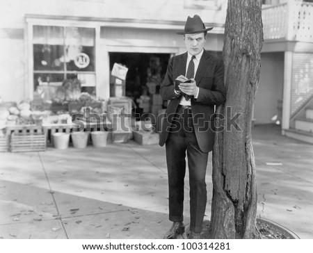 Detective leaning against tree taking notes