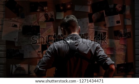 Detective looking at investigation board, searching for solution, back view