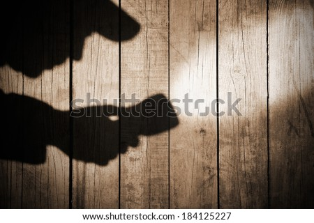 Detective Silhouette with a searchlight on Grungy Wooden Background.  #184125227
