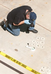 Detective studying a crime scene taking photographs