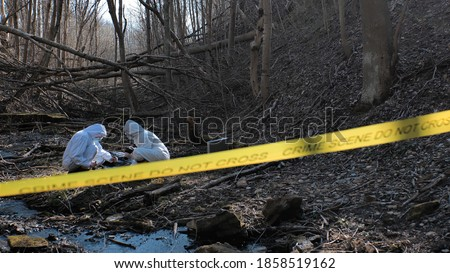 Detectives are collecting evidence in a crime scene. Forensic specialists are making expertise. Police investigation in a forest. Stockfoto ©