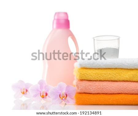 Detergent for washing machine in laundry with towels and flower in the white background.