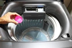 Detergent, hands and cloth in washing machine