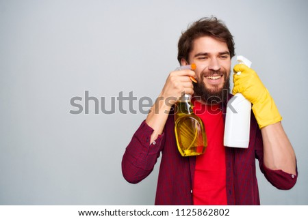 Detergent in the hands of a man, a red T-shirt and a claret shirt                            #1125862802