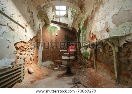deteriorated prison cell walls and barber chair