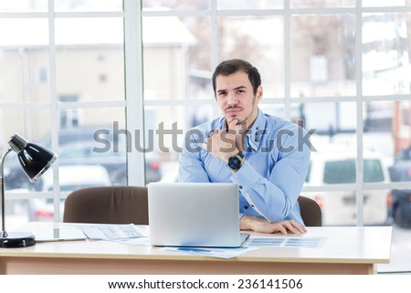 Determination in business. Confident businessman working at a laptop and holding a hand under her head while businessman sitting in office at the table.