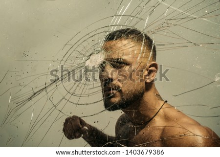 Determination to succeed. Muscular man having inner determination and commitment to break glass wall. Determined latino man removing obstacle with determination and confidence. Determination concept.