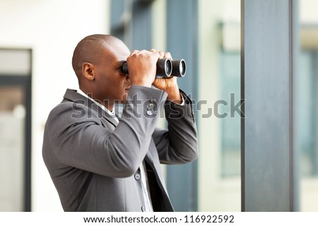 determined african american businessman using binoculars in office