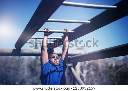 Determined boy exercising on monkey bar during obstacle course in boot camp #1250932159