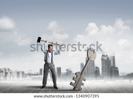 Determined businessman against cityscape breaking with hammer stone key figure #1340907395