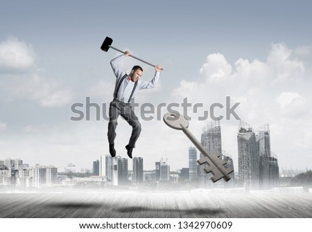 Determined businessman against cityscape breaking with hammer stone key figure #1342970609