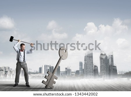 Determined businessman against cityscape breaking with hammer stone key figure #1343442002