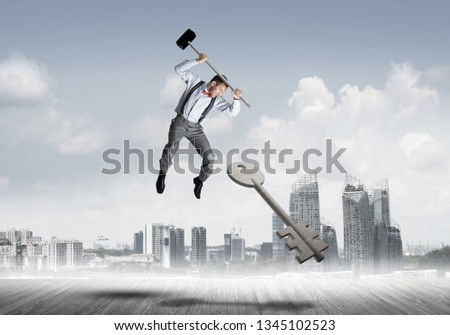 Determined businessman against cityscape breaking with hammer stone key figure #1345102523