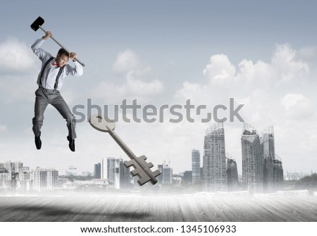 Determined businessman against cityscape breaking with hammer stone key figure #1345106933