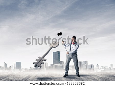 Determined businessman against cityscape breaking with hammer stone key figure #688328392